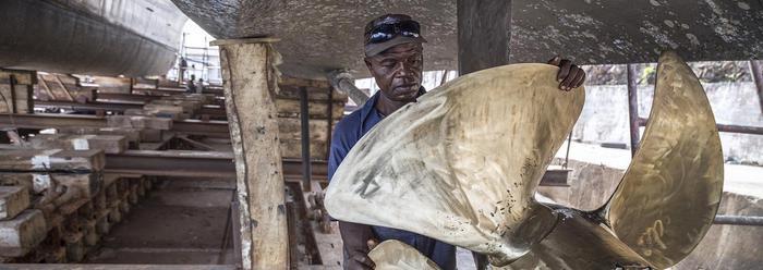 Werknemer uit Sierra Leone aan het werk op de scheepswerf